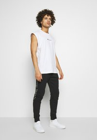 Champion - TAPE PANTS - Spodnie treningowe - black - 1