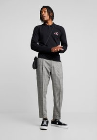 Calvin Klein Tailored - GLENCHECK PLEATED TAPERED PANT - Trousers - black - 1