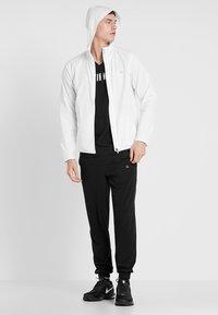 Calvin Klein Performance - PANTS - Tracksuit bottoms - black/bright white - 1