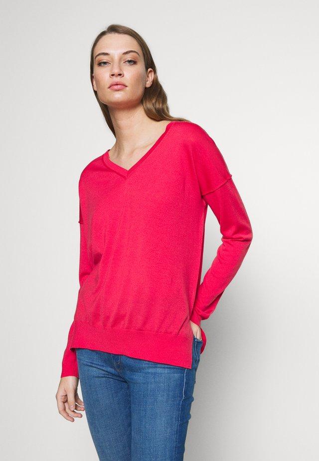 Stickad tröja - geranium