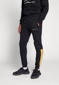 CLOSURE London - CONTRAST SCRIPT JOGGER - Pantalon de survêtement - black/mustard - 0