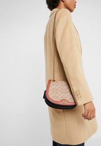 Coach - COATED SIGNATURE PARKER SADDLE BAG - Across body bag - tan rust - 1