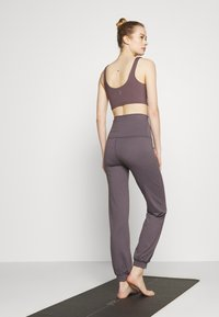 Curare Yogawear - LONG PANTS ROLL DOWN - Tracksuit bottoms - purple - 2