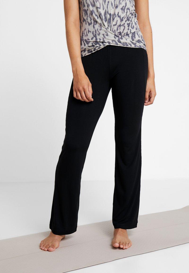 Curare Yogawear - PANTS FLARED LEGS - Teplákové kalhoty - black