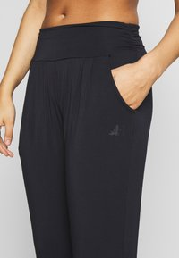 Curare Yogawear - PANTS LONG LOOSE ROLL DOWN - Tracksuit bottoms - midnight blue - 4