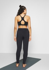 Curare Yogawear - PANTS LONG LOOSE ROLL DOWN - Tracksuit bottoms - midnight blue - 2