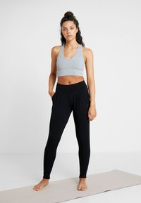 Curare Yogawear - PANTS LONG LOOSE ROLL DOWN - Träningsbyxor - black