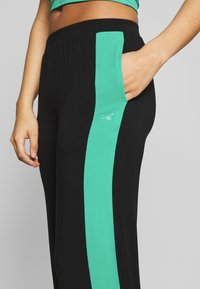 Curare Yogawear - PANTS WIDE GALON STRIPE - Trainingsbroek - black/green lagoon - 4