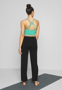 Curare Yogawear - PANTS WIDE GALON STRIPE - Trainingsbroek - black/green lagoon - 2