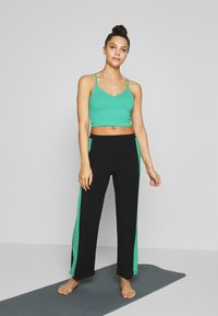Curare Yogawear - PANTS WIDE GALON STRIPE - Trainingsbroek - black/green lagoon - 1