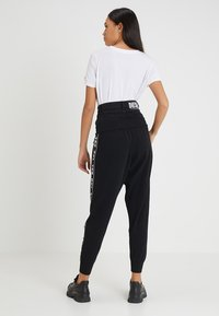 Diesel - M-SUIT-A TROUSERS - Pantalones deportivos - black - 2