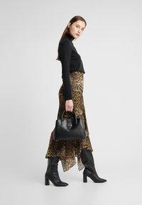 DKNY - LYLA CENTER ZIP SATCHEL SUTTON - Handbag - black/gold - 1