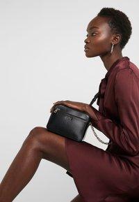DKNY - BRYANT CAMERA BAG SUTTON - Across body bag - black/gold - 1