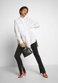 DKNY - WHITNEY MINI DOME SATCHEL - Handbag - black/gold - 1