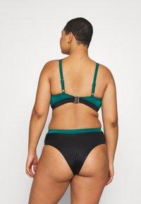 DORINA CURVES - ATTICANON PADDED PLUNGE - Bikinitopp - green - 2