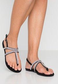 Dorothy Perkins - FARAWAY T-BAR TOEPOST - Sandály s odděleným palcem - black - 0