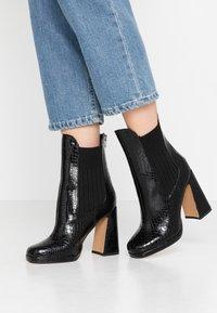 Dorothy Perkins - LOLA SKYE LOOPER ASYMETRIC SQUARE TOE BOOT - High heeled ankle boots - black - 0