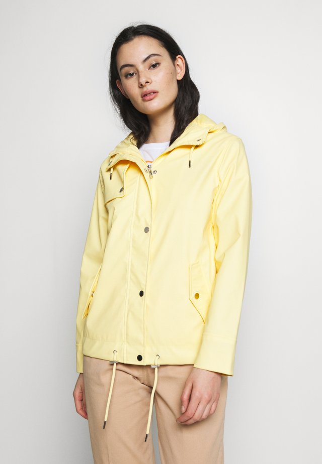 SHORT RAINCOAT - Waterproof jacket - ochre