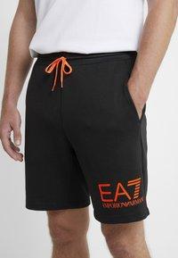 EA7 Emporio Armani - Tracksuit bottoms - black/neon/orange - 6