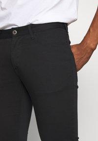 Emporio Armani - TESSUTO - Trousers - nero - 3
