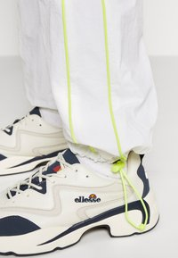Ellesse - DELLA X SMILEY - Tracksuit bottoms - white