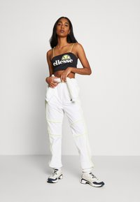 Ellesse - DELLA X SMILEY - Tracksuit bottoms - white - 1
