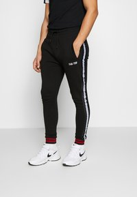 FAKTOR - STITULA - Tracksuit bottoms - black - 0
