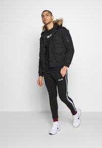 FAKTOR - STITULA - Tracksuit bottoms - black - 1