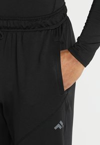 FIRST - TRAINING PANTS - Tracksuit bottoms - black - 3