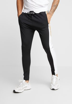 TROUSERS WITH FOIL PRINT - Tracksuit bottoms - black