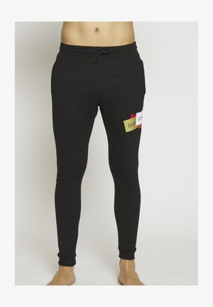 STICKERS JOGGERS - Tracksuit bottoms - black