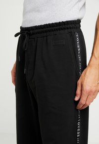 Guess - ZEPH PANTS - Trainingsbroek - jet black - 4