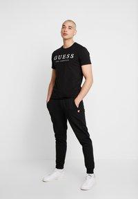 Guess - ADAM PANTS - Spodnie treningowe - jet black - 1
