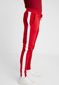 Guess - JAMES PANTS - Spodnie treningowe - red white combo - 4