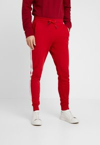 Guess - JAMES PANTS - Spodnie treningowe - red white combo - 0