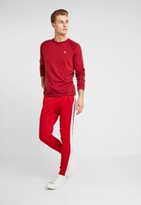 Guess - JAMES PANTS - Spodnie treningowe - red white combo - 1