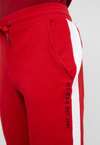 Guess - JAMES PANTS - Spodnie treningowe - red white combo - 3