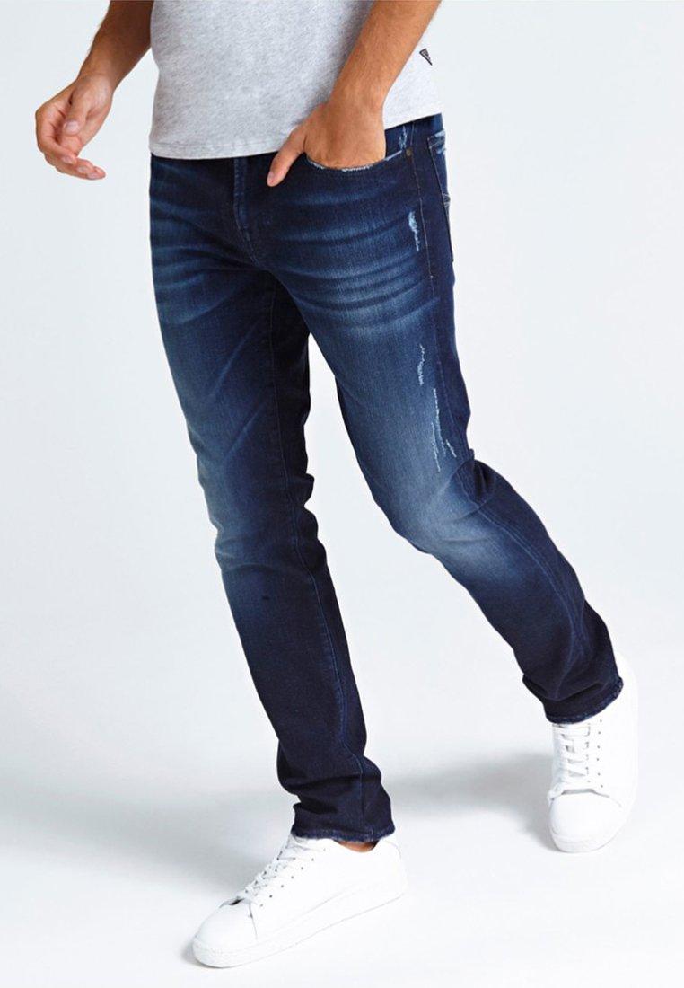 Guess - SLIJTPLEKKEN - Jeans slim fit - blue