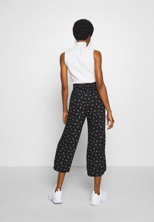 CHAIN WIDE LEG - Trousers - black