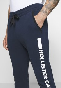 Hollister Co. - PRINT LOGO - Tracksuit bottoms - navy - 3