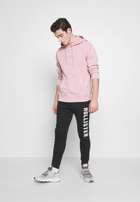 Hollister Co. - ICONIC LOGO  - Tracksuit bottoms - black - 1