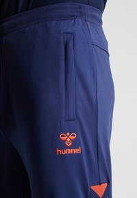 Hummel - HMLNATHAN PANTS - Pantalon de survêtement - black iris/grenadine - 4