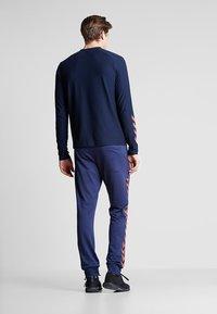 Hummel - HMLNATHAN PANTS - Pantalon de survêtement - black iris/grenadine - 2