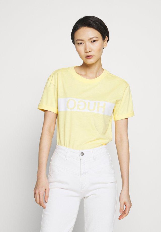 DATINA - Printtipaita - light pastel yellow