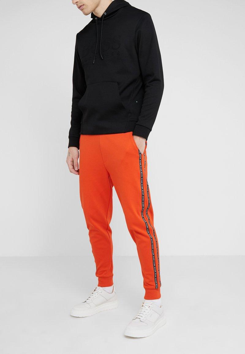 HUGO - DRAPANI - Tracksuit bottoms - dark orange