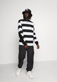 Hummel Hive - OVERSIZED PANTS - Pantalones - black - 1