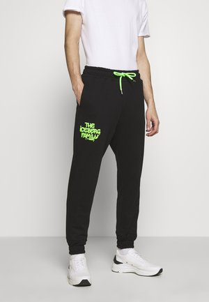VANDAL - Tracksuit bottoms - black/green