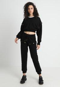 Ivy Park - ARMOUR POPPERS CROP - Sweatshirt - black - 1