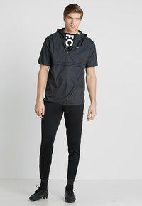 JAKO - ACTIVE - Pantalones deportivos - schwarz/neongelb - 1