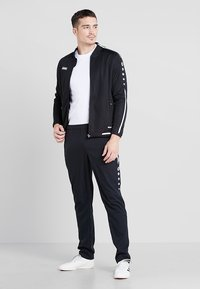 JAKO - STRIKER - Pantalon de survêtement - schwarz/weiß - 1
